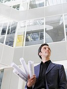 Business man holding rolled blueprints under arm in atrium of office building low angle view
