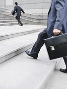 Business men hurrying up steps outdoors side view (thumbnail)