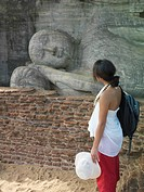 Young woman looking at statue of sleeping Buddha side view