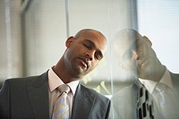 Tired businessman leaning head on window