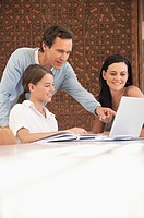 Parents helping daughter with a laptop