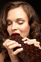 Woman enthusiastically eating a chocolate bar