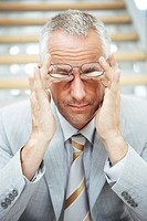 Businessman rubbing his eyes
