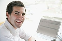Friendly businessman at desk with laptop