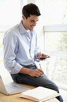 Casual businessman sitting on desk with cell phone