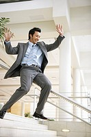 Businessman sliding down stairway railing