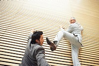 Two businessmen fighting while climbing a wall