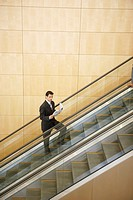 Businessman standing on escalator reading
