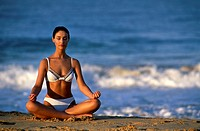 Young woman meditating in the lotus position on the beach