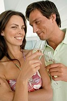 Close-up of a mid adult couple toasting with champagne flutes