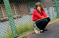 Young woman crouching near a chain-link fence