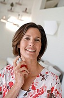 Portrait of a mature woman spraying perfume and smiling
