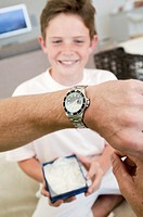 Close-up of a man´s hand wearing a wrist watch with his son sitting in the background