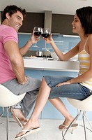 Side profile of a mid adult couple toasting with wine glasses