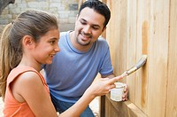 Father and daughter staining fence (thumbnail)