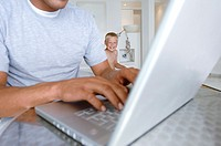 Mid section view of a man using a laptop and his son sitting behind him
