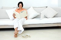 Mature woman sitting on a couch looking at a photo album and smiling