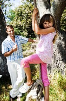 Side profile of a girl holding a rope swing with her father holding an apple in the background