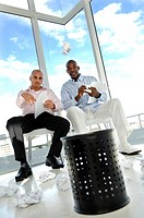 Portrait of two businessmen sitting in chairs and throwing paper balls in a paper basket
