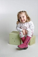 A young girl sitting on building blocks