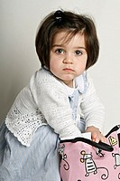 A young girl reaching her hand into a mouse print handbag