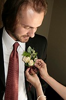 A woman helps a bridegroom with his buttonhole flower on his wedding day