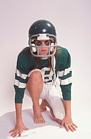 A young boy posed in scrum position wearing a full American football uniform