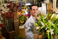 A man stands in a florist holding a bunch of flowers
