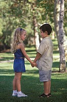 Two children holding hands and looking at each other in a park