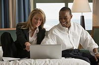 Businessman and businesswoman sitting on bed and looking at laptop