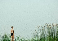 Young woman in swimsuit standing by edge of water