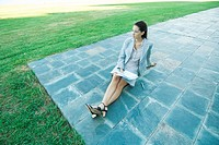 Businesswoman sitting on ground on patio, holding documents