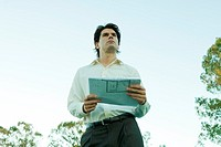 Man holding blueprints, low angle view