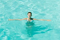 Young woman in pool with arms out and eyes closed