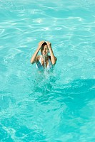 Young woman splashing water over face in pool