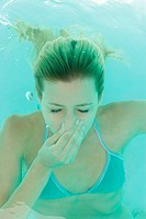 Young woman holding nose underwater