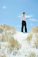 Businessman standing on dune, looking down at cell phone