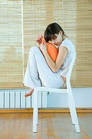 Young woman sitting on chair with knees up, holding cushion (thumbnail)