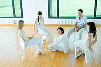 Group therapy, man sitting on floor in center of circle of adults sitting in chairs