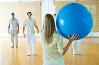 Group therapy, woman throwing ball to group