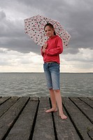 Girl 11-13, standing on wooden pier, holding umbrella, portrait