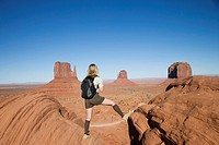 USA, Arizona, Monument Valley, woman standing on rocks, rear view