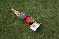 Boy6-8 lying on grass using laptop