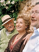 Senior couple and mature son sitting in garden, smiling, close-up
