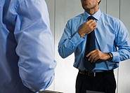 Businessman adjusting tie in front of mirror