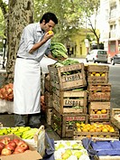 Young man eating fruit from street market stall