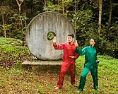 Couple doing tai chi in front of sculpture in jungle