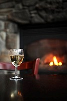 Glass of white wine on table, fireplace in background focus on wine