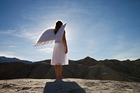 Woman wearing angel wings standing on rocks, full length