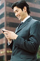 Businessman looking at mobile phone, smiling